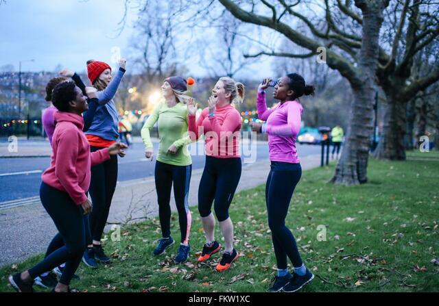 Six female adult runners celebrating on city verge at dusk - Stock Image