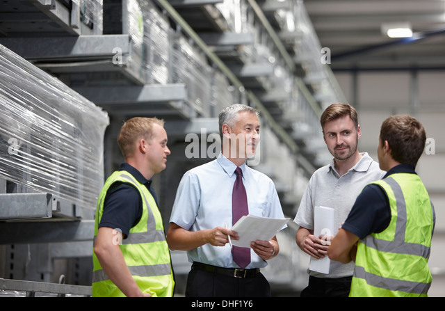 Warehouse workers and manager meeting in engineering warehouse - Stock Image
