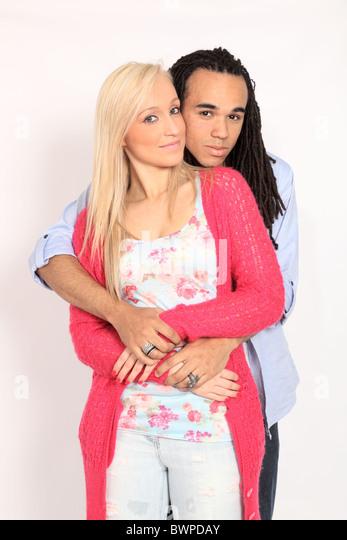 Blond girl and boy with dreadlocks cuddling - Stock Image