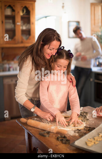 Mother and daughter cutting shapes in dough to make homemade cookies - Stock Image
