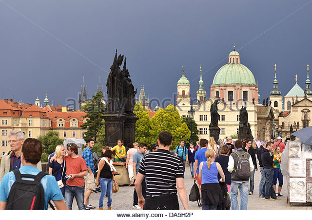 Prague Czech Republic - people walking across the historical Charles Bridge with dark sky above. - Stock Image