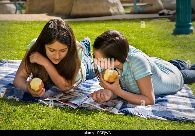 13 year old Vietnamese/Caucasian and Hispanic/Caucasian girls read together in park. MR  © Myrleen Pearson - Stock-Bilder