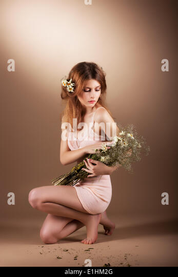 Sentimental Auburn Barefoot Woman Relaxing with Wildflowers - Stock Image