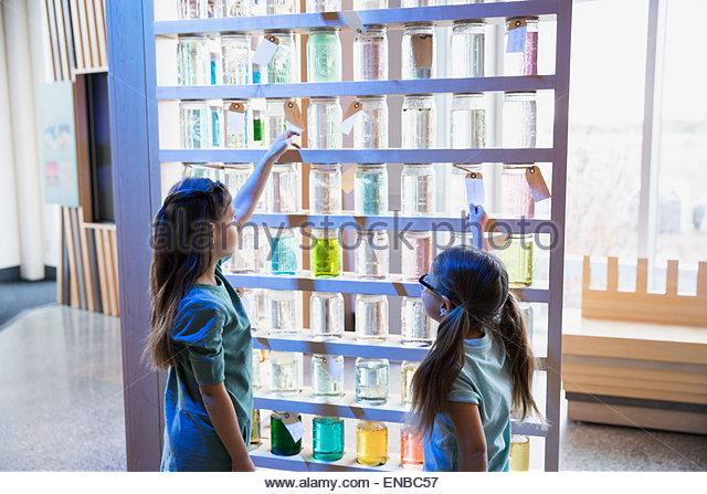 Sisters viewing jar display at science center - Stock Image
