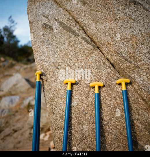 Whitewater paddles lined up along a boulder. - Stock Image