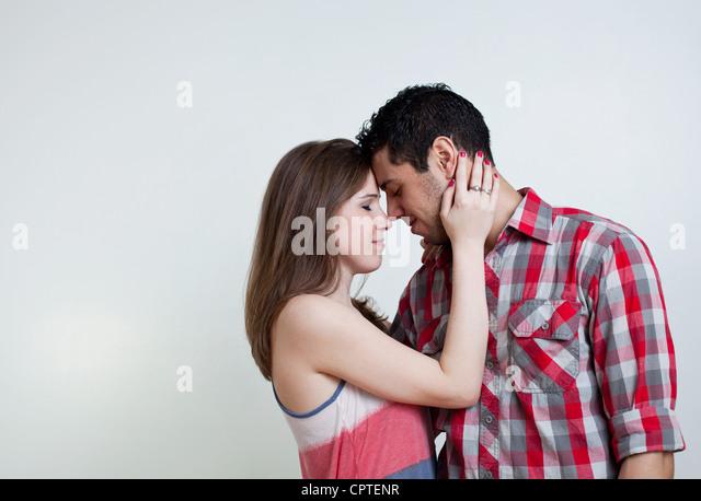 Young couple embracing, studio shot - Stock Image