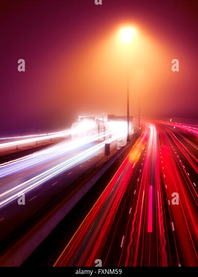 Busy highway traffic light trails on a misty night, Highway 401, Toronto, Ontario, Canada - Stock Image