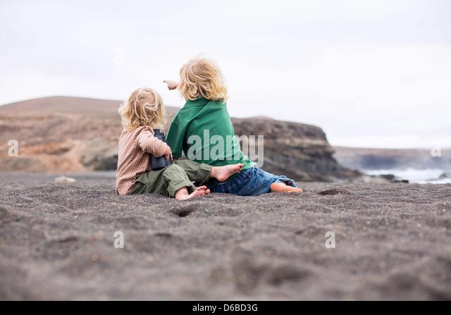 Children sitting in sand on beach - Stock-Bilder