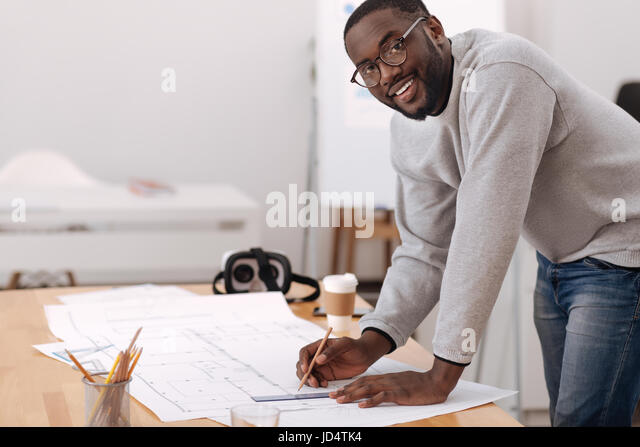 Positive handsome man leaning over the table - Stock Image