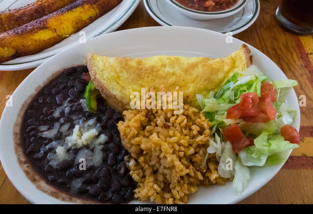 Mexican brunch: omelette, black beans, cheese, brown rice, salad, plantains, salsa and beer Stock Photo