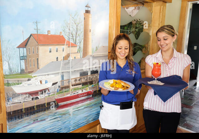Wisconsin Kenosha Simmons Island Bluefish Restaurant Kenosha Yacht Club lighthouse mural Hispanic girl teen waitress - Stock Image