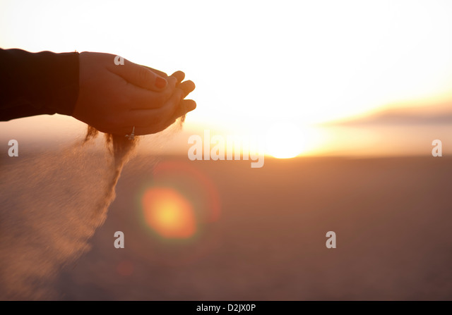 womans hands with sand flowing through at sunset - Stock Image