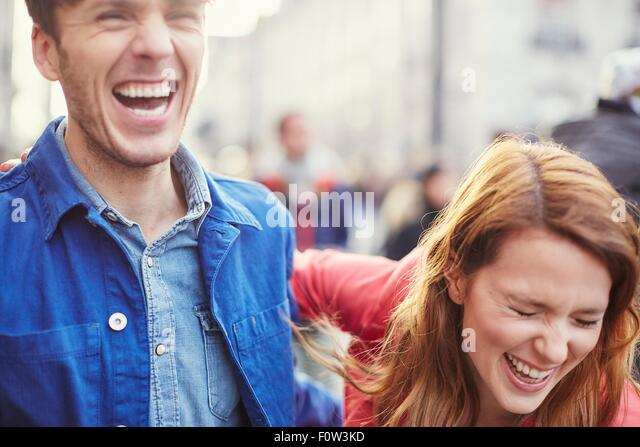 Couple laughing on street, London, UK - Stock Image