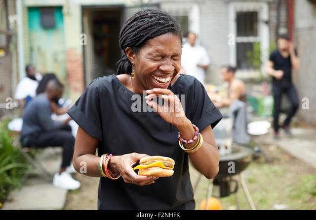 African American woman eating at backyard barbecue - Stock Image