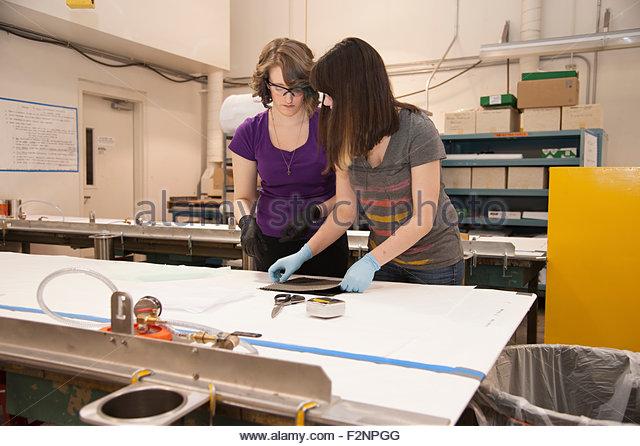 Caucasian women working on machinery in workshop - Stock-Bilder