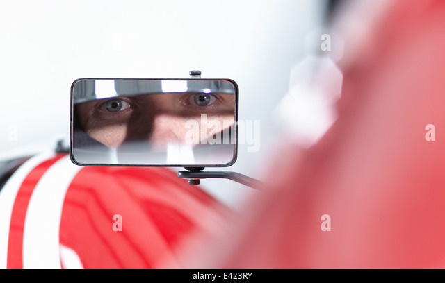 Portrait of racing car driver reflected in wing mirror of supercar - Stock Image