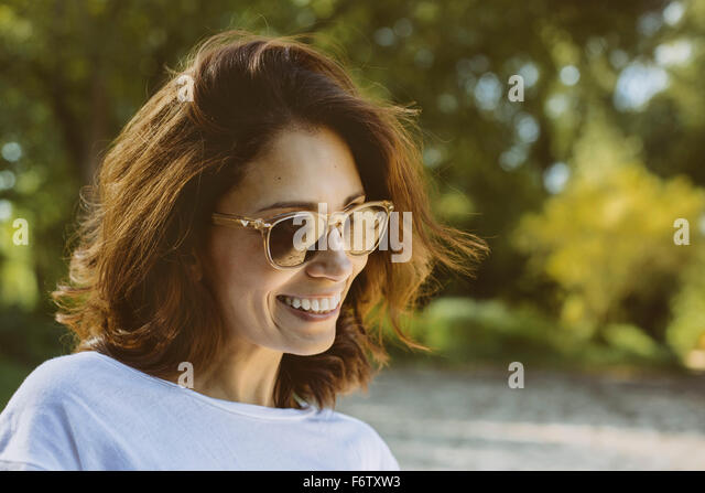 Portrait of smiling woman with brown hair wearing sunglasses - Stock Image