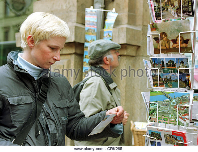 A young woman chooses from Postcards - Stock Image