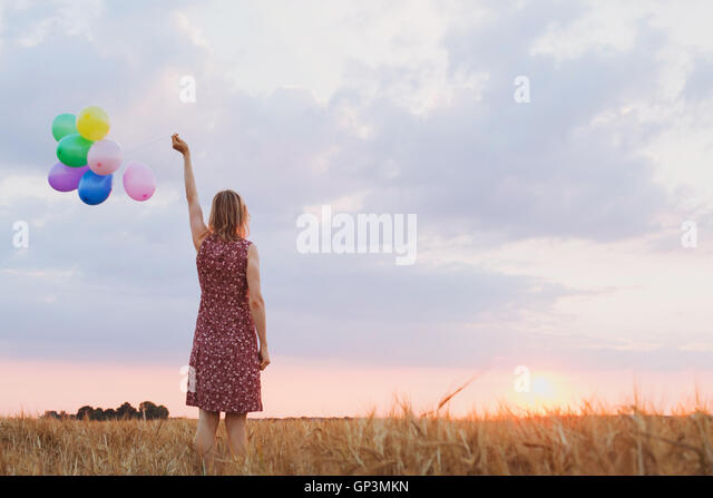 hope concept, emotions and feelings, woman with colourful balloons in the field, background - Stock Image