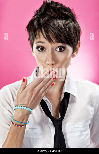 A young woman with funky short brown hair covering her mouth, wearing a button down shirt and necktie. - Stock Image