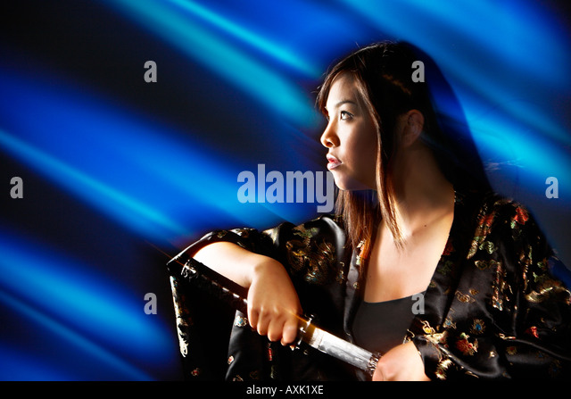 Asian warrior fighting girl woman lady with sword looking up hair silk blue black brown silver - Stock Image