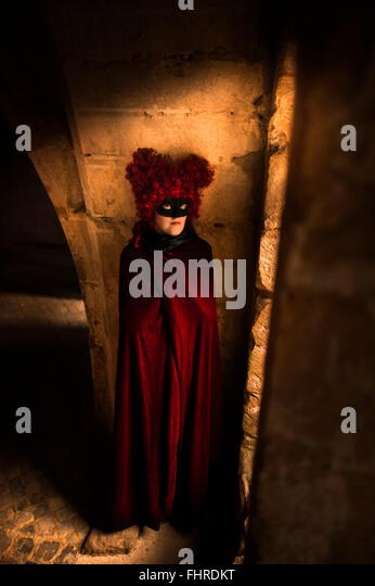 female figure wearing red wig  standing in castle by the window - Stock Image
