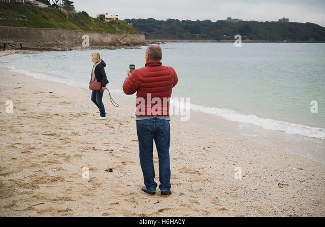 Man takes a photograph of a woman on Falmouth's Gyllyngvase Beach - Stock Image