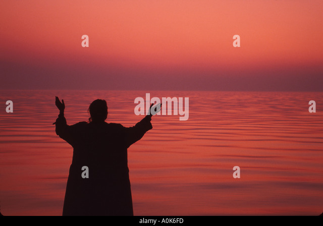 Russia former Soviet Union St. Petersburg Gulf of Finland woman with raised arms at dusk - Stock Image