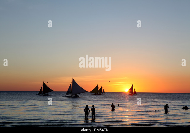 Sail boats ply the shore line at sunset on White Beach, Boracay, the most famous tourist destination in the Philippines. - Stock-Bilder