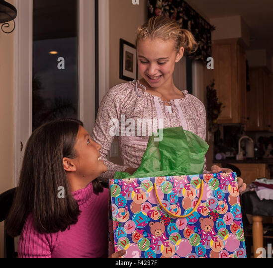 Child giving gift to child interracial multicultural multi ethnic Korean and Brazilian best girl friends opening - Stock-Bilder