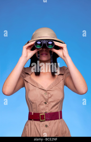 A woman wearing a pith helmet searching with a pair of binoculars blue background with copy space - Stock Image