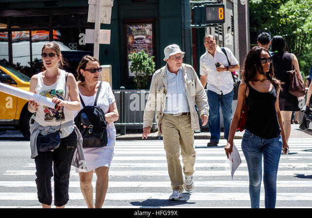 Manhattan New York City NYC NY Midtown Turtle Bay intersection Second Avenue Black woman man senior walking crossing - Stock Image