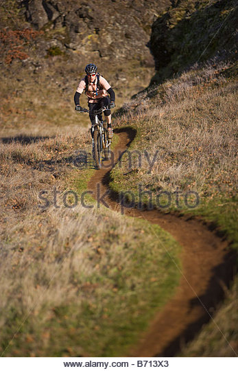 A man riding a mountain bike on singletrack trail in Washington state. - Stock Image