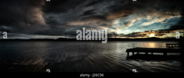 Sunset over the Lake of Varese with dramatic clouds in the sky and pier in the foreground, autumn season - Stock Image