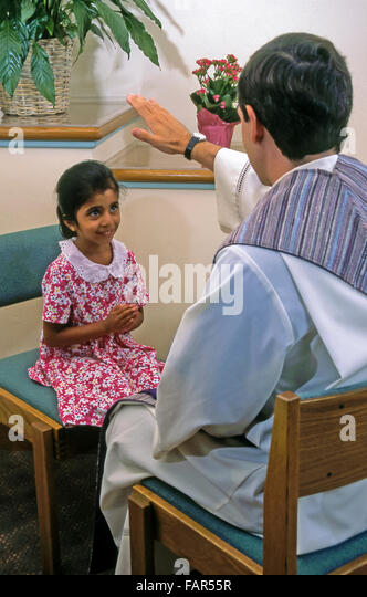 White priest with his hand raises blesses 6 year years old girl wearing pink floral dress during reconciliation - Stock-Bilder