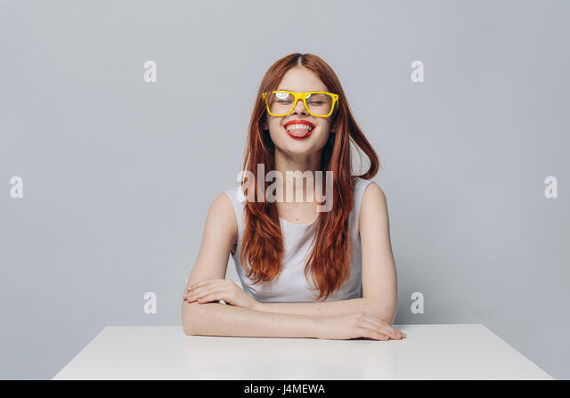 Caucasian woman sitting at table with tongue out - Stock-Bilder