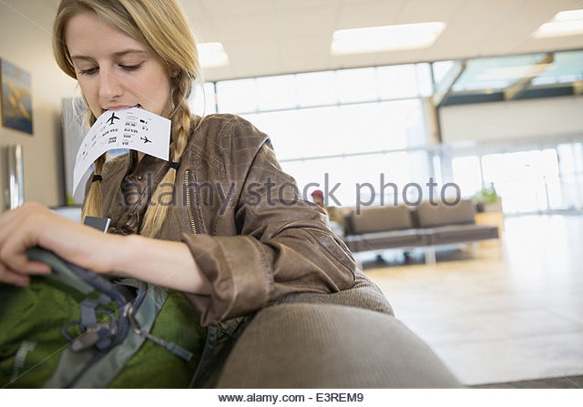 Woman looking inside backpack at airport - Stock Image