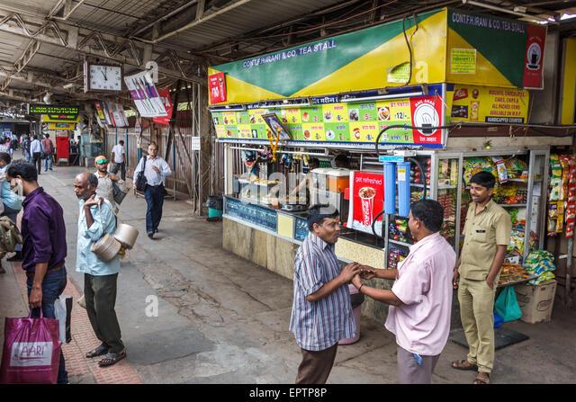 Mumbai India Asian Charni Road Railway Station Western Line train public transportation platform man stall concession - Stock Image