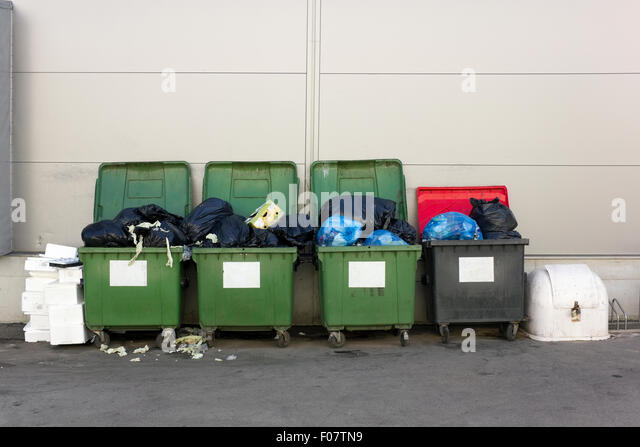 Green and black  garbage containers  near large food city  market shop. Concept of environmental pollution - Stock Image