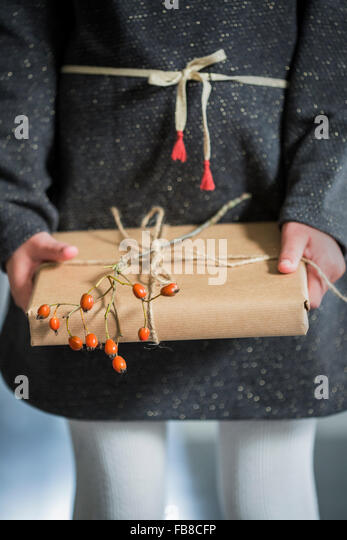 Sweden, Girl (6-7) holding wrapped Christmas present - Stock Image