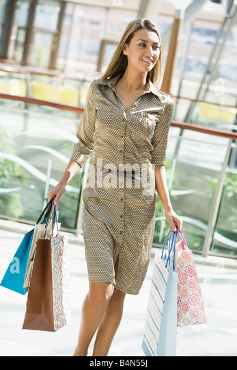 Woman walking in mall smiling (selective focus) - Stock Image