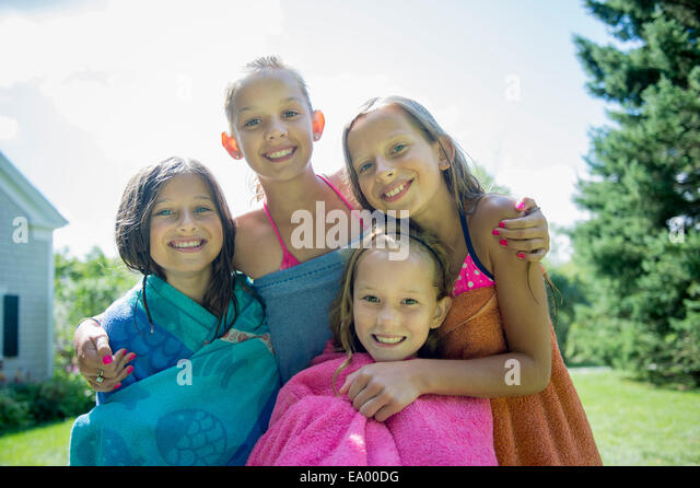 Girls in swimming costume wrapped in towels - Stock Image