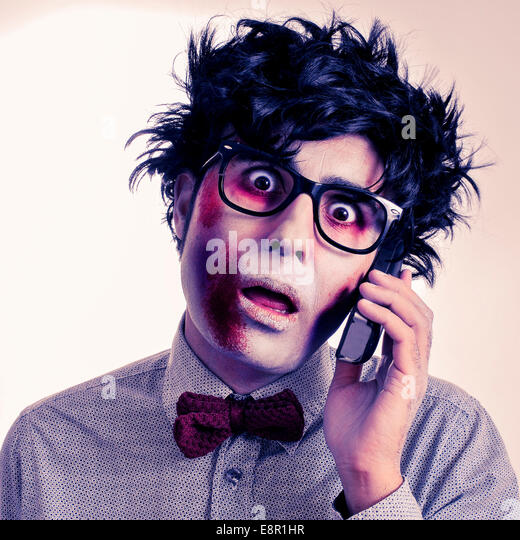 a scary hipster zombie with black plastic-rimmed eyeglasses talking on the phone, with a retro effect - Stock-Bilder