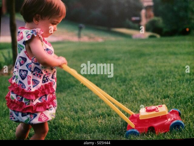 A toddler girl cuts the grass with a toy lawn mower - Stock Image