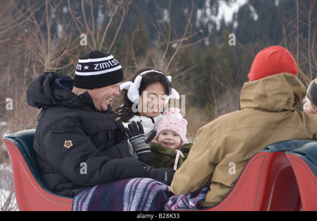 Family enjoys a sleigh ride Whistler British Columbia Canada - Stock Image