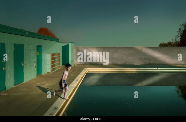 Canada|, British Columbia, Greater Vancouver Regional District, Vancouver, Boy (10-11) jumping into swimming pool - Stock Image