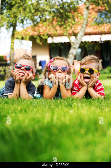 Trio children showing their tongues - Stock-Bilder
