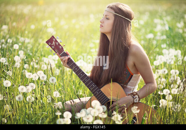 Hippie woman with guitar in summer meadow . Nature harmony - Stock Image