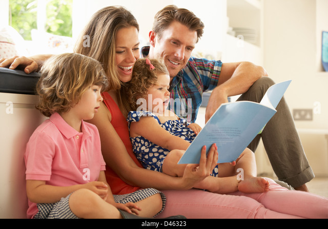 Parents Sitting With Children Reading Story Indoors - Stock Image
