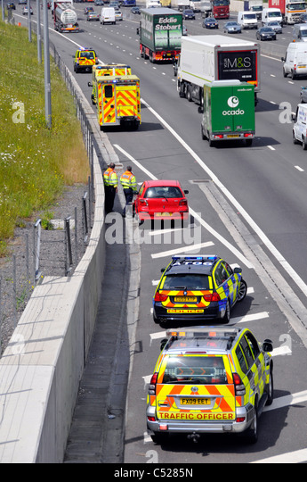 View from above looking down on red car after motorway crash moved to hard shoulder parked emergency services vehicles - Stock Image